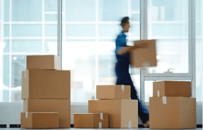 Image of a man moving boxed and packing up office supplies