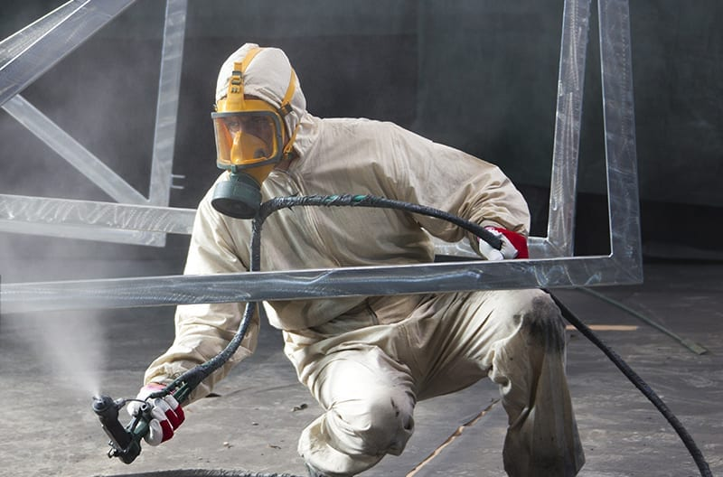 Person in full industrial protective clothing doing industrial abrasive sandblasting on steel structure by East Coast Protective Coatings.