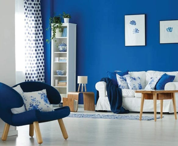 A living room with white floor and blue wall, with blue chair, white lounge and white bookcase