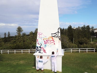2 Newcastle Painting Services team members painting the Obelisk in Newcastle