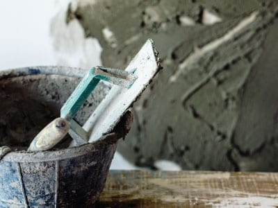 Plastering tool with a plastered wall in the background
