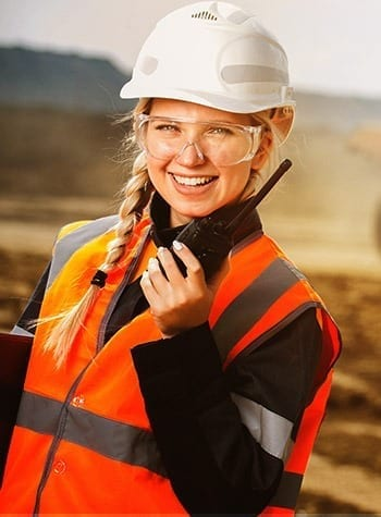 woman using two-way radio on a mine site