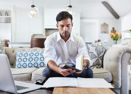 Hispanic businessman working on laptop and writing notes in living room at home
