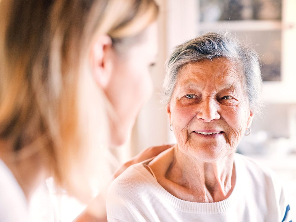 Woman speaking with elderly woman psychology counselling